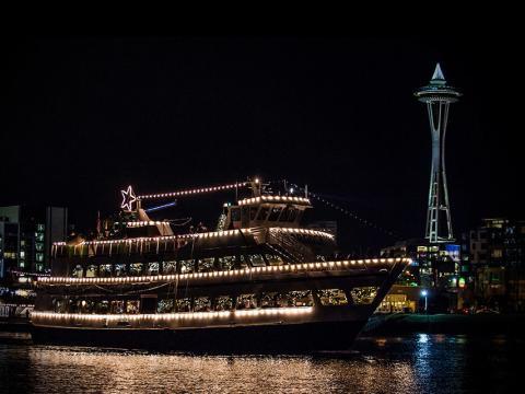 Un bateau illuminé passant devant la Space Needle pendant le festival Argosy Christmas Ships & Bonfires